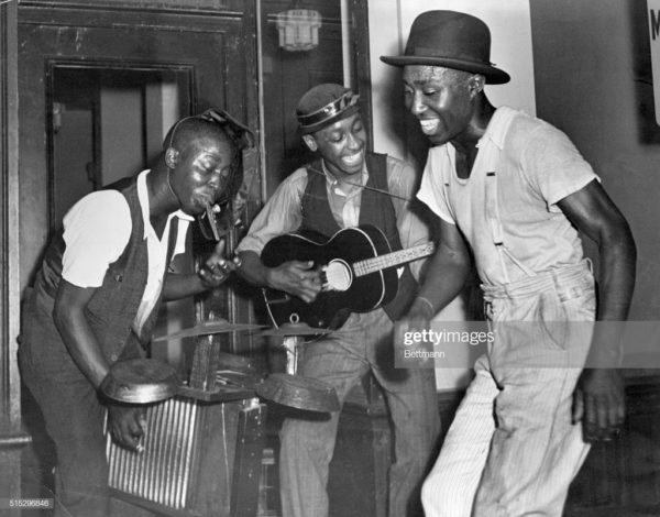 Members from a folk music band featuring a drum set made from pie tins and a washboard play together.